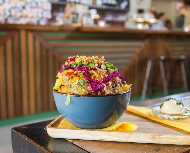 Zbliżenie naczynie z ziemniakami, mięsem i pokrojonymi warzywami w pucharze z zamazanym tłem