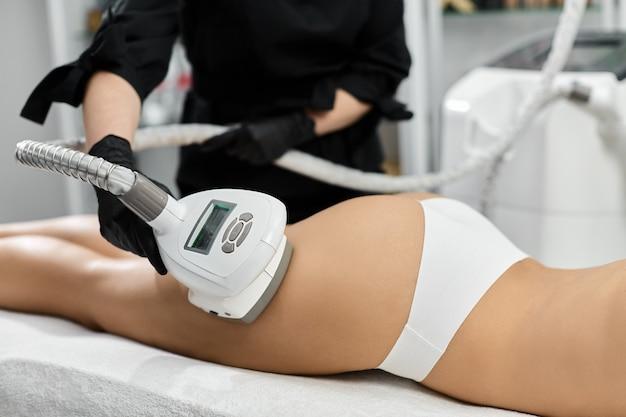 Zbliżenie: nagie ciało kobiety otrzymującej terapię endosferą na nogę w spa