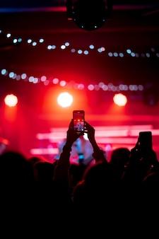 Zbliżenie nagrywania wideo za pomocą smartfona podczas koncertu. stonowany obraz