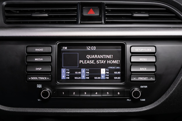 """Zbliżenie napisu na monitorze nawigatora samochodowego """"kwarantanna! zostań w domu!"""". koncepcja powszechnej kwarantanny. pandemia wirusów i przemysł samochodowy"""