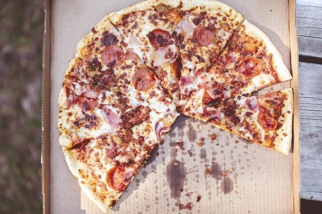 Zbliżenie narzutów pysznej pizzy w środowisku zewnętrznym
