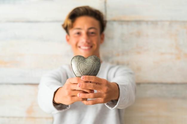 Zbliżenie nastolatka trzymającego metalowe serce w domu z drewnianym tłem - oy dający koncept serca