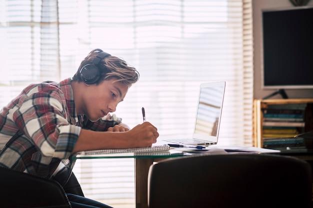 Zbliżenie nastolatka ze słuchawkami wpatrującego się w laptopa odrabiającego pracę domową w ciszy - facet skupienia się na pomieszczeniu
