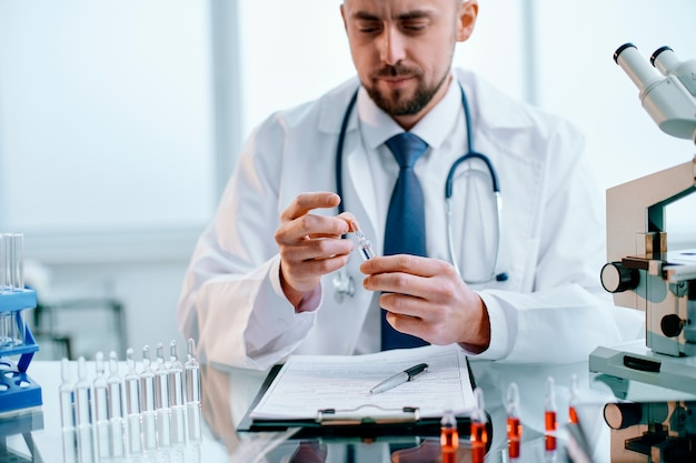 Zbliżenie naukowiec patrząc na ampułkę ze szczepionką