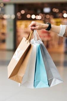 Zbliżenie nie do poznania kobiety trzymającej stertę toreb na zakupy w centrum handlowym
