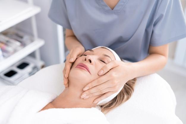 Zbliżenie: nie do poznania profesjonalista kosmetyczny, dając masaż twarzy zrelaksowanej dojrzałej kobiecie w salonie piękności
