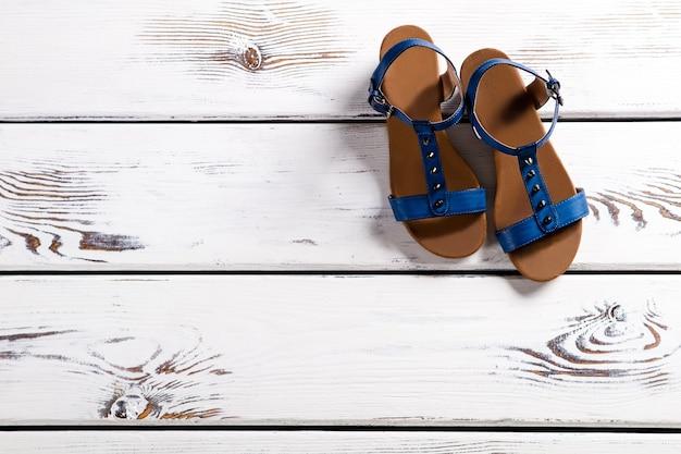 Zbliżenie: niebieskie sandały kobiety. kobiece sandały na drewnianej półce. letnie obuwie z małą klamrą. buty dziewczęce na lato.