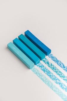 Zbliżenie niebieskiego koloru pastelowa kredka pisze kredą nad własną linią śladową