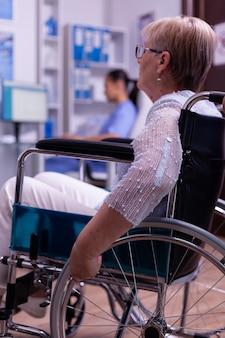 Zbliżenie niepełnosprawnej, sparaliżowanej, niepełnosprawnej starszej kobiety na wózku inwalidzkim, czekającej na badanie lekarskie w korytarzu szpitala