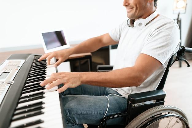 Zbliżenie niepełnosprawnych męskich rąk gra syntezator.