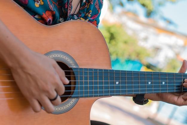 Zbliżenie: nierozpoznawalna kobieta grająca na gitarze akustycznej w parku