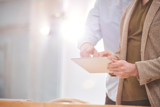 Zbliżenie nierozpoznawalnego biznesmena za pomocą tabletu podczas badania informacji online z kolegą