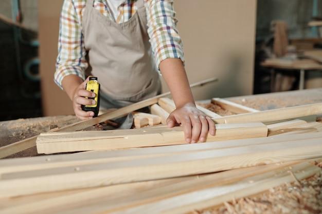 Zbliżenie nierozpoznawalnego chłopca w fartuchu za pomocą centymetra podczas pracy z drewnianymi detalami w warsztacie stolarskim