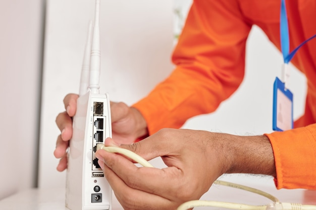 Zbliżenie nierozpoznawalnego czarnego mężczyzny z plakietką łączącą kabel internetowy z routerem podczas konfigurowania bezprzewodowego punktu dostępowego