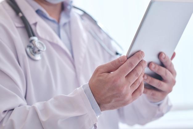 Zbliżenie nierozpoznawalnego lekarza w fartuchu laboratoryjnym za pomocą cyfrowego tabletu podczas analizy internetowych notatek medycznych