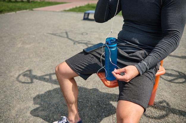 Zbliżenie nierozpoznawalnego męskiego ciała sportowca z butelką świeżej wody w rękach, smartfonem na kolanie, noszeniem słuchawek, siedzącym na nieruchomo na boisku sportowym na świeżym powietrzu
