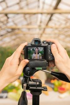 Zbliżenie nierozpoznawalnego operatora kamery przygotowującego się do nagrywania wideo przeglądu produktów rolnych