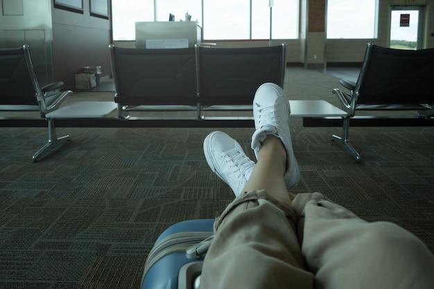 Zbliżenie nierozpoznawalnego podróżnika z nogami na walizce czekającej na lotnisku, kopia przestrzeń