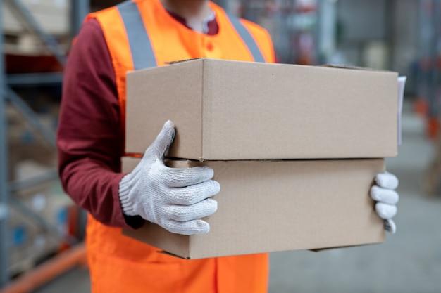Zbliżenie nierozpoznawalnego pracownika magazynu niosącego pudełka podczas sortowania w magazynie