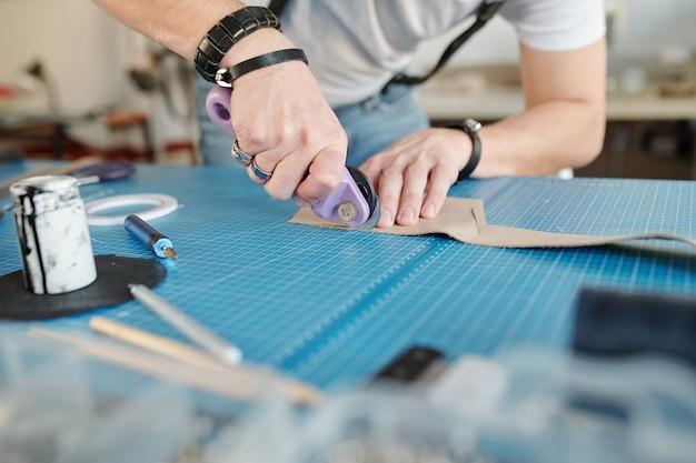 Zbliżenie nierozpoznawalnego robotnika z pierścieniami krawędzi tnącej skóry na macie do cięcia w studio rzemieślniczym