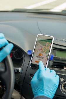 Zbliżenie nierozpoznawalnego taksówkarza w lateksowych rękawiczkach wciskającego przycisk na ekranie dotykowym podczas rozpoczynania podróży taksówką