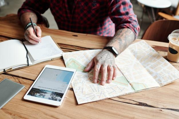 Zbliżenie nierozpoznawalnego wytatuowanego mężczyzny siedzącego przy stole w kawiarni i sprawdzającego położenie hotelu na mapie podczas planowania podróży