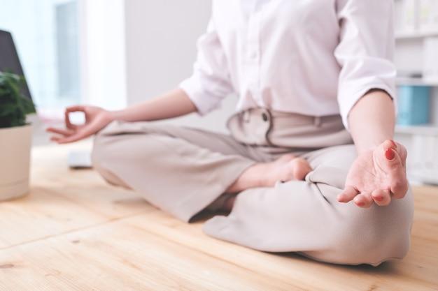 Zbliżenie nierozpoznawalnej bizneswoman siedzącej w pozycji lotosu i trzymającej się za ręce w mudrze podczas ćwiczeń relaksującej medytacji w miejscu pracy