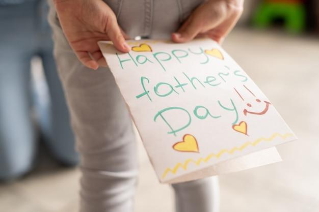 Zbliżenie nierozpoznawalnej dziewczyny trzymającej kreatywną kartę dnia ojca z sercami za plecami, przygotowując się do świętowania ukochanego ojca