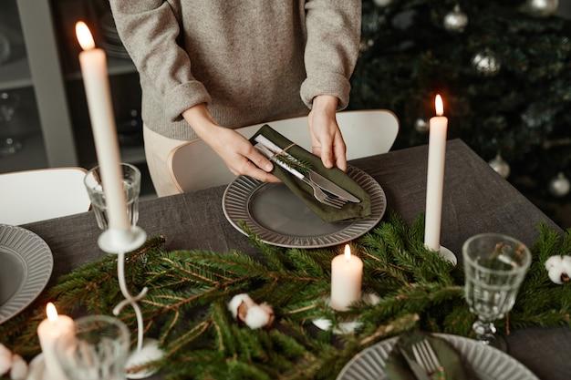 Zbliżenie nierozpoznawalnej kobiety nakrywającej świąteczny stół ozdobiony gałązkami jodły i...