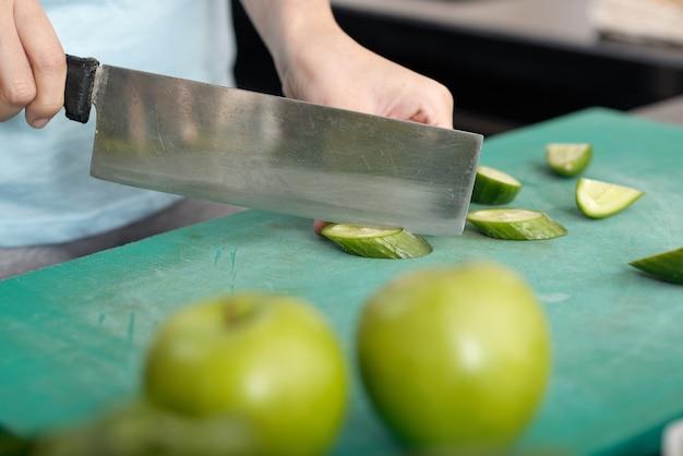 Zbliżenie nierozpoznawalnej kobiety używającej noża do warzyw podczas krojenia ogórka na pokładzie