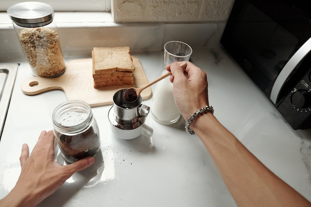 Zbliżenie: nierozpoznawalny mężczyzna z bransoletką wkładający zmieloną kawę do zaparzacza podczas robienia kawy w kuchni