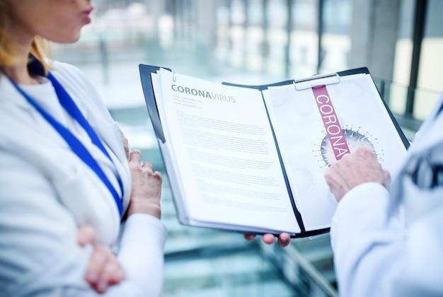 Zbliżenie nierozpoznawalnych lekarzy rozmawiających o koronawirusie na konferencji, brzuch.