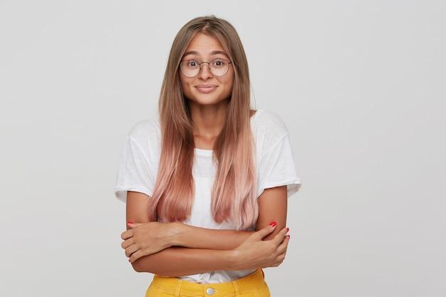 Zbliżenie nieśmiała uśmiechnięta młoda kobieta z długimi farbowanymi pastelowymi różowymi włosami nosi koszulkę i okulary czuje się zawstydzona i trzyma ręce złożone na białym tle nad białą ścianą