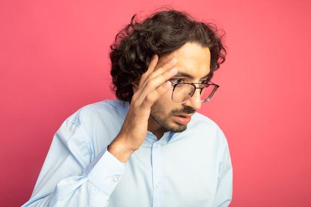 Zbliżenie niespokojny młody przystojny mężczyzna w okularach dotykając głowy patrząc na bok na białym tle na różowej ścianie