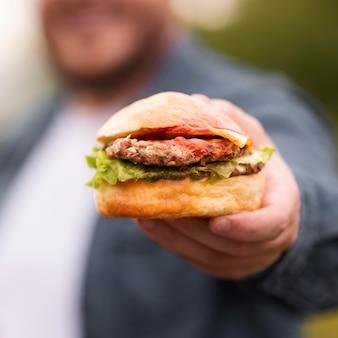 Zbliżenie niewyraźne mężczyzna trzyma burgera