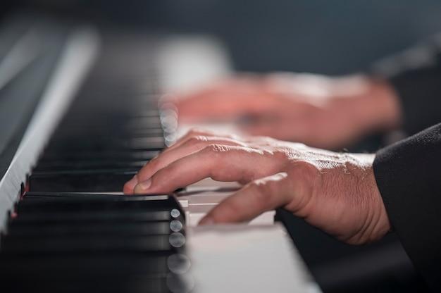 Zbliżenie niewyraźne ręce grające na pianinie cyfrowym