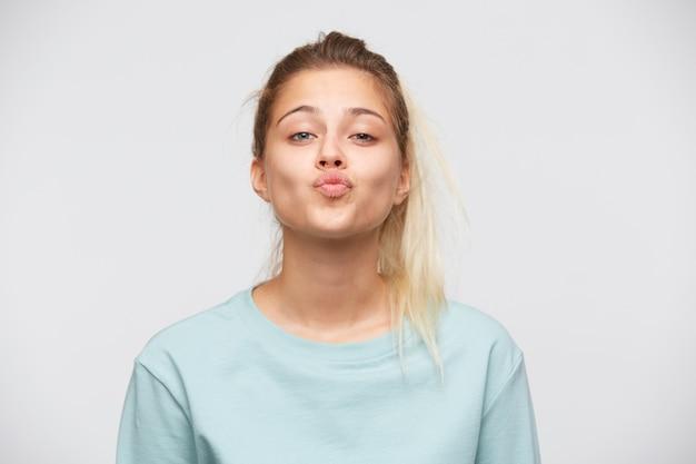 Zbliżenie niezadowolona ładna młoda kobieta z blond włosami i kucykiem nosi niebieską koszulkę