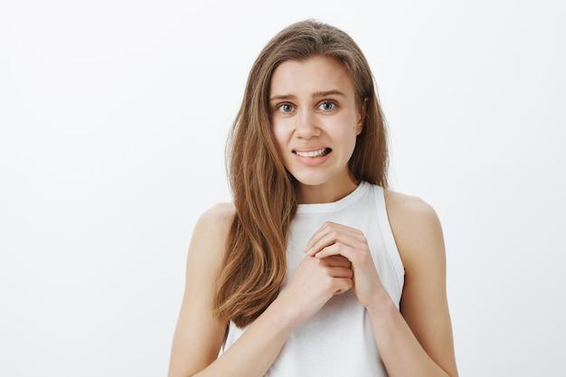 Zbliżenie niezręcznej i przestraszonej nieśmiałej dziewczyny, która boi się zadać pytanie