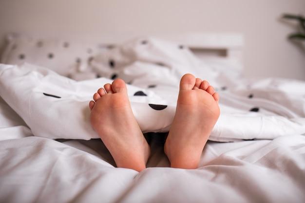 Zbliżenie nóg dziecka spod kocyka na łóżku
