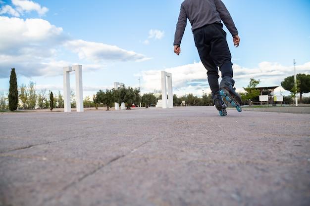 Zbliżenie nogi z rolkami w akcji w pięknym parku miejskim