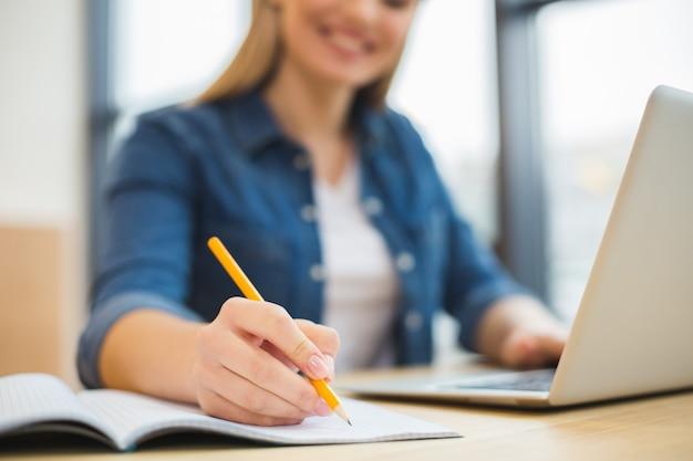 Zbliżenie notatek robionych przez inteligentną miły wesoły kobietę podczas pracy w biurze