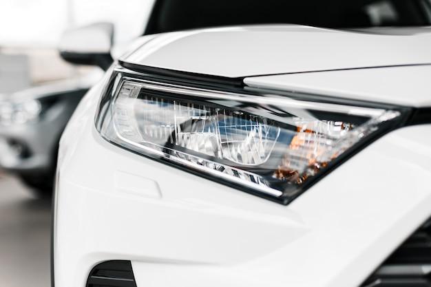 Zbliżenie nowoczesne i luksusowe reflektory samochodowe. szczegóły i biały samochód
