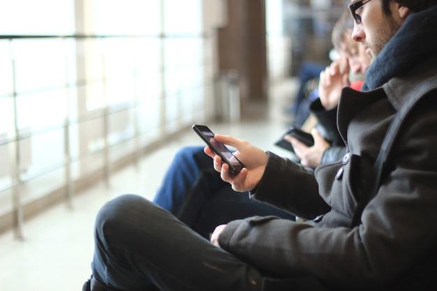 Zbliżenie nowoczesnego człowieka ze smartfonem siedzącym w budynku lotniska