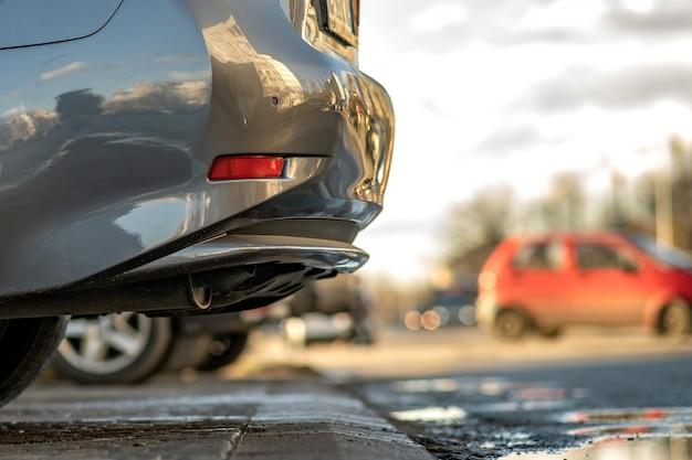 Zbliżenie nowożytni samochody parkujący na stronie miasto ulica w słonecznym dniu.