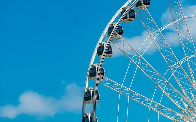 Zbliżenie nowożytny ferris koło przeciw niebieskiemu niebu i bielowi chmurnieje