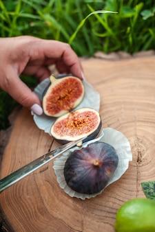 Zbliżenie nożem w ramie tnie figi na drewnianej okrągłej desce