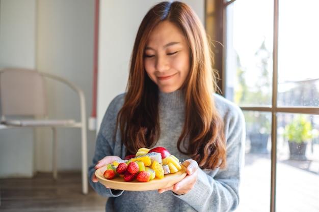 Zbliżenie obraz azjatyckiej kobiety trzymającej drewniany talerz świeżych mieszanych owoców na szaszłykach