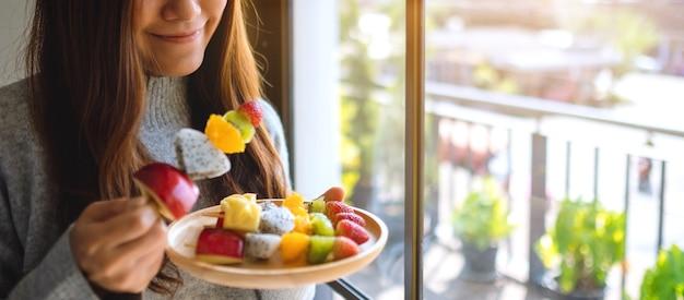 Zbliżenie obraz azjatyckiej kobiety trzymającej i jedzącej świeże mieszane owoce na szaszłykach