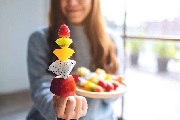 Zbliżenie obraz azjatyckiej kobiety trzymającej i pokazującej świeże mieszane owoce na szaszłykach