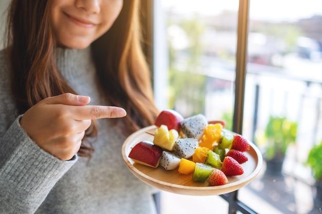 Zbliżenie obraz azjatyckiej kobiety trzymającej palec wskazujący na drewnianym talerzu świeżych owoców mieszanych na szaszłykach